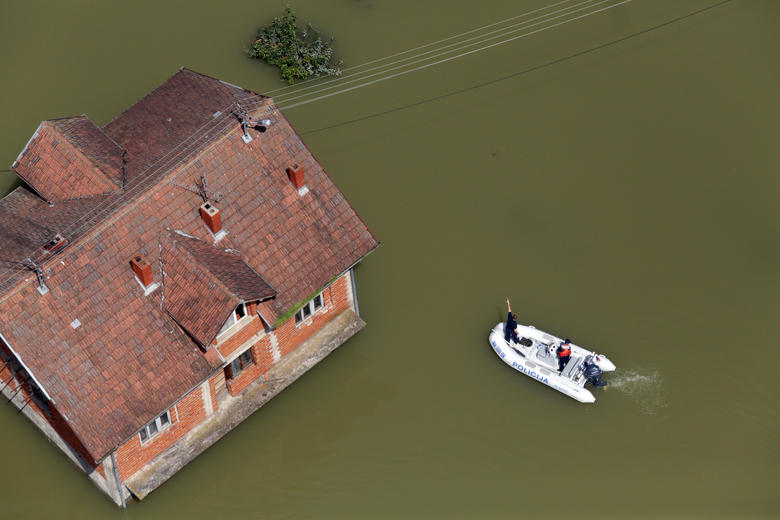 Flooded House Overseen By A Police Boat