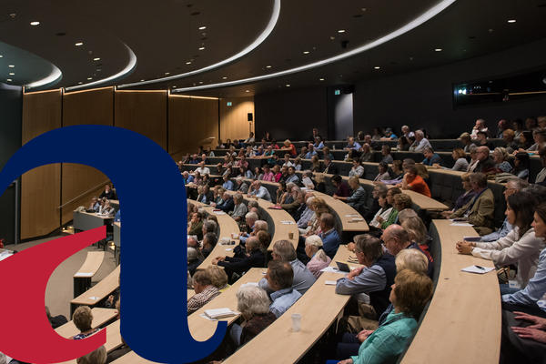 A full lecture theatre, during a Meeting Minds event, with the alumni logo imposed on the left of the picture