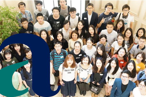 A group picture of an Alumni group, with the alumni logo imposed on the left of the picture