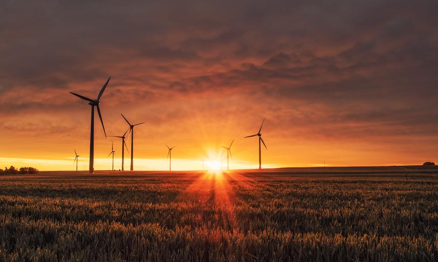Wind turbines against a sunset